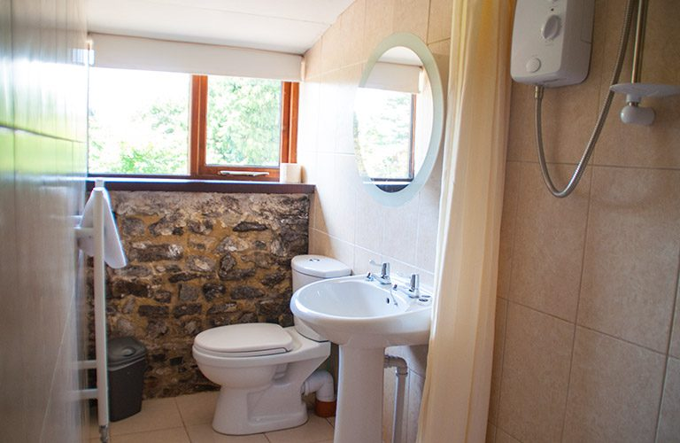 Bathroom/ wetroom, with sink, toilet, heated towel rail and electric shower