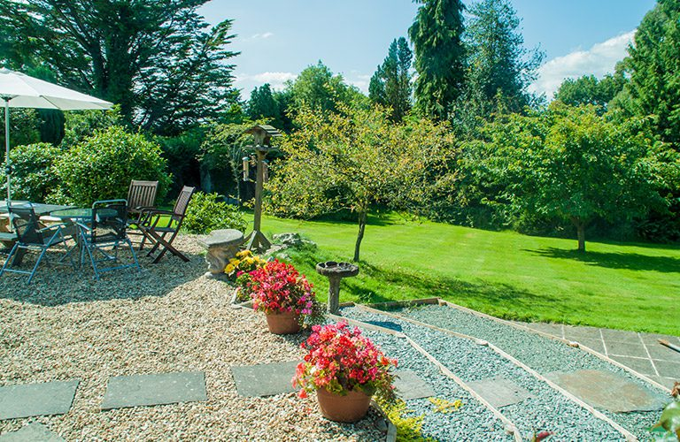 Green grass with seating area and flower tubs