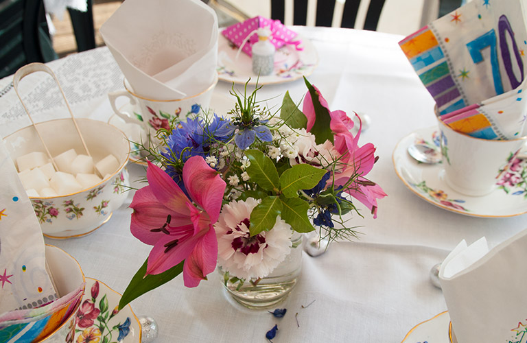 Table flowers along with china plates and sugar bowl