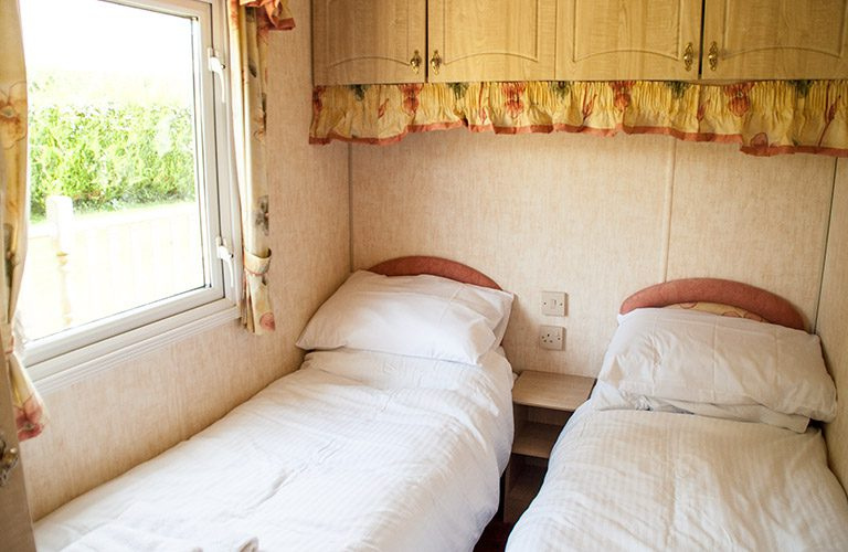 Twin beds in the mobile home with a window looking out over the garden