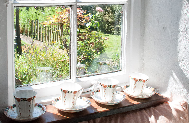 Four fine china teacups on a window sill with the sun beaming in
