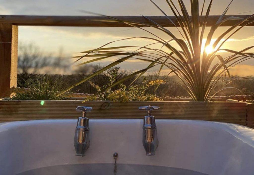 enjoying the sunset in an outdoor bath on the deck of luxury cabin in Devon
